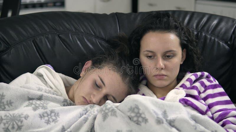 Mädchen in den pijamas, die auf der Couch mit Decke und Uhr Fernsehen sitzen lizenzfreie stockbilder