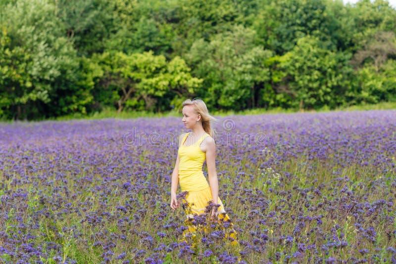 Mädchen in den purpurroten Blumen draußen im Sommer stockfoto