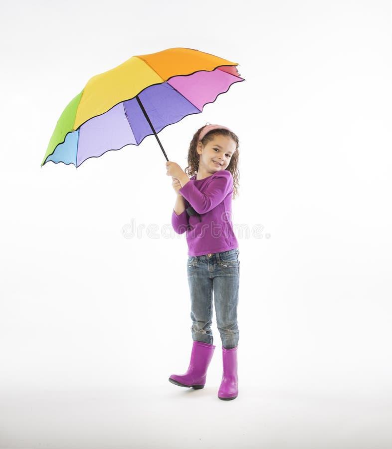 Mädchen in den rosa Regenstiefeln mit Regenbogenregenschirm lizenzfreie stockfotografie