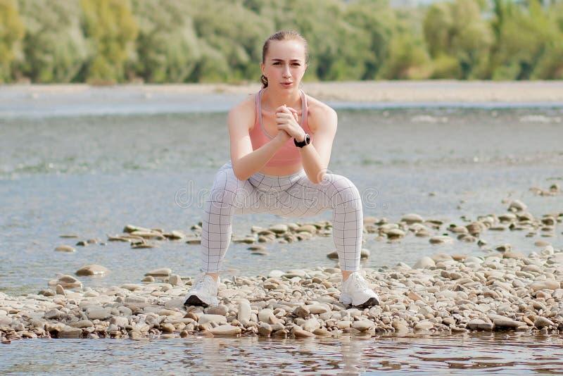 Mädchen in den Sportuniformen macht eine Ausdehnung auf der Flussbank lizenzfreies stockfoto