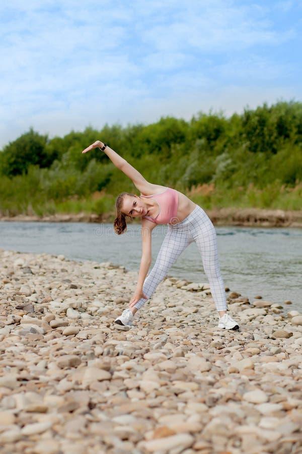 Mädchen in den Sportuniformen macht eine Ausdehnung auf der Flussbank lizenzfreie stockfotos