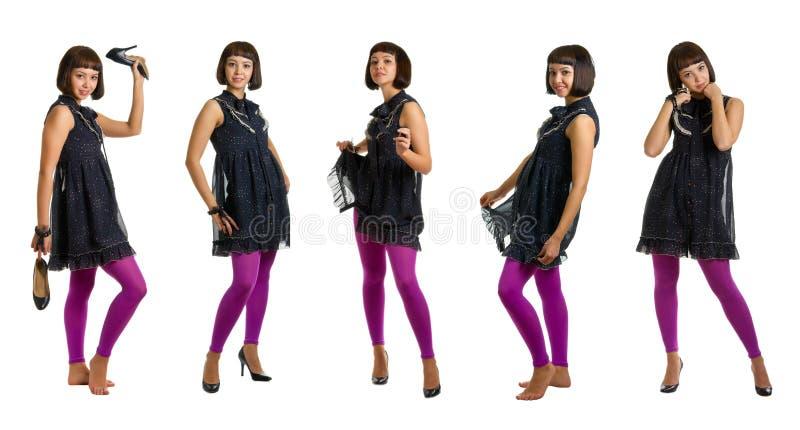 Mädchen in den Strümpfen eines dunklen Kleides und der Flieder lizenzfreie stockfotografie