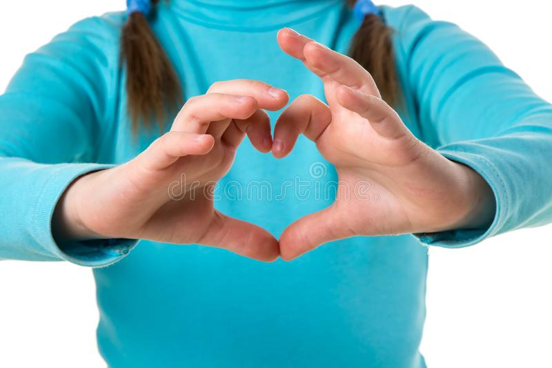 Mädchen in der blauen Strickjacke mit den Händen in der Herzform nah oben lizenzfreies stockfoto