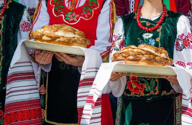 Mädchen in der ethnischen bulgarischen Kleidung, die traditionelles schönes Laib hält lizenzfreies stockbild