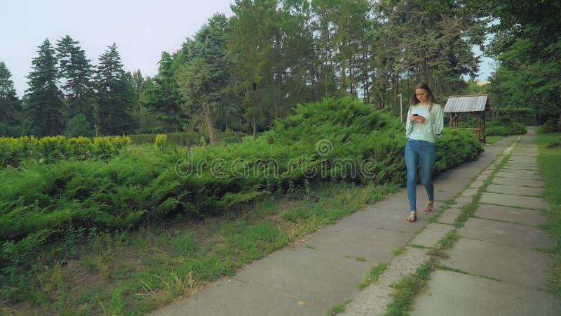 Mädchen in der grünen Bluse geht auf die Bahn mit dem Telefon, wirft Mitteilungen und seitlich Blick stockbilder
