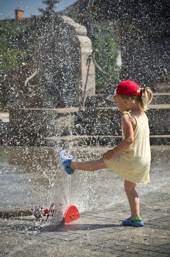 Mädchen in der heißen Sommerstadt mit Wasserberieselungsanlage stockfoto