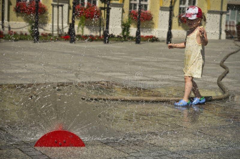 Mädchen in der heißen Sommerstadt mit Wasserberieselungsanlage lizenzfreies stockbild