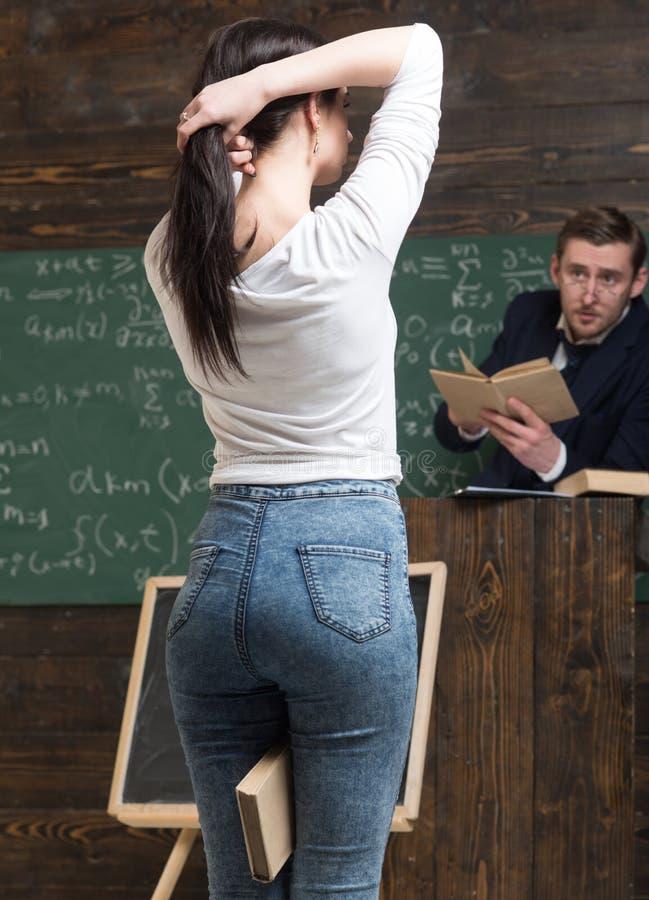 Mädchen der hinteren Ansicht mit dem netten Kolben, der einen Pferdeschwanz beim Halten eines Buches zwischen ihren Beinen herste lizenzfreie stockfotos