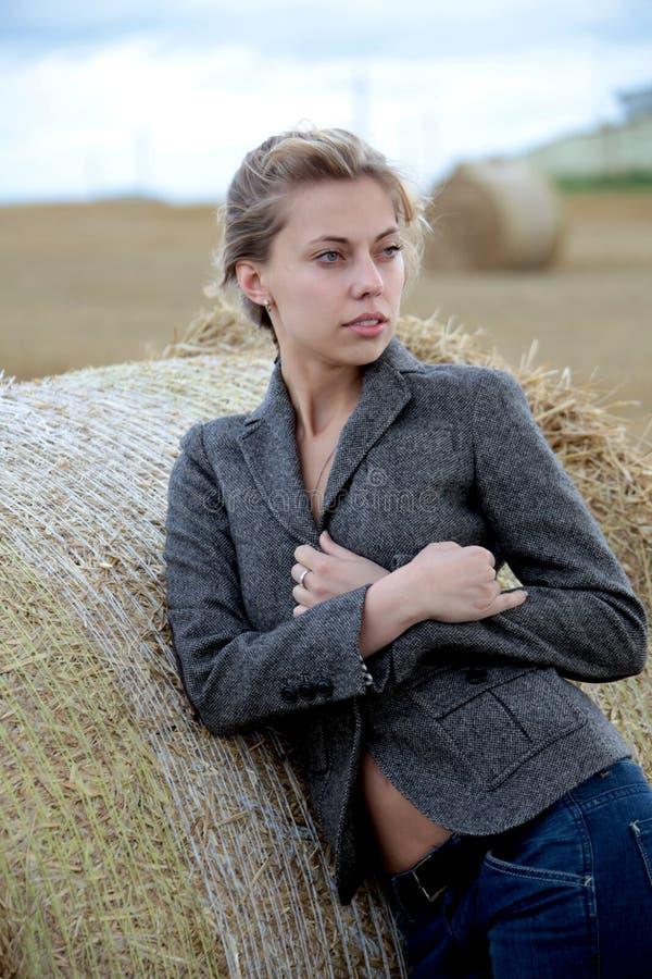 Mädchen in der Jacke auf dem Gebiet lizenzfreies stockfoto