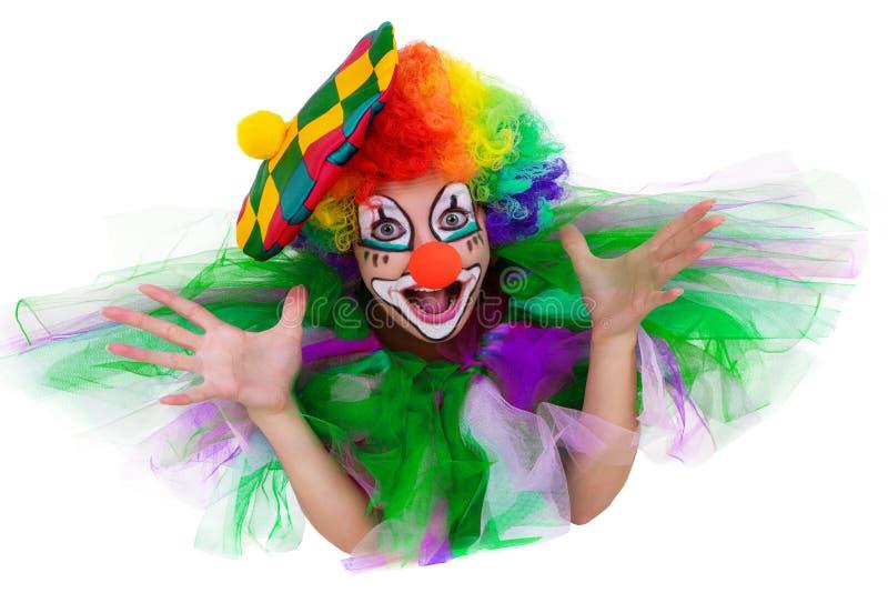 Mädchen in der Kappe und im Clown, die Kostüm mit einem Blumenstrauß von Blumen heraus die Zunge setzt, schaut oben stockfotografie