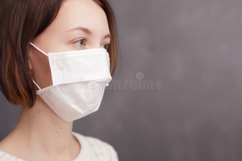 Mädchen in der medizinischen Wegwerfmaske, welche die Kamera betrachtet lizenzfreie stockfotos