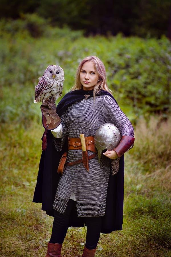 Mädchen in der mittelalterlichen Rüstung, eine Eule halten stockfotos