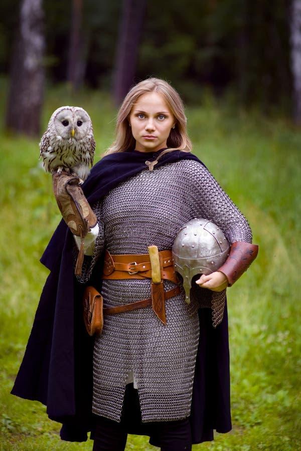 Mädchen in der mittelalterlichen Rüstung, eine Eule halten stockbild