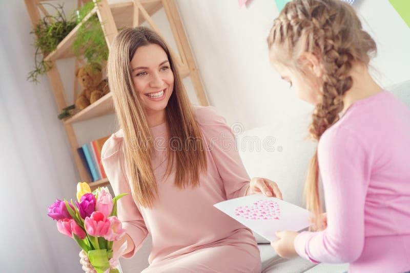 Mädchen der Mutter- und Tochterzusammen zu Hause Frauen Tages, dasihrer Mutter Geschenke gibt stockbilder