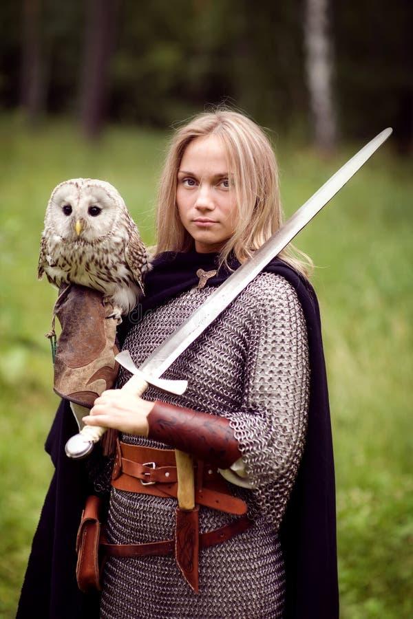 Mädchen in der Rüstung und mit einer Klinge, die eine Eule hält stockbilder