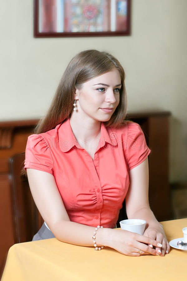 Mädchen in der roten Bluse sitzt in einem Restaurant an einem Tisch mit a stockfotografie
