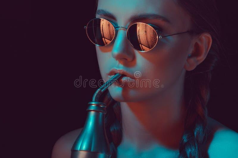 Mädchen in der runden Sonnenbrille Soda von der Wasserflasche mit Stroh trinkend lizenzfreies stockfoto