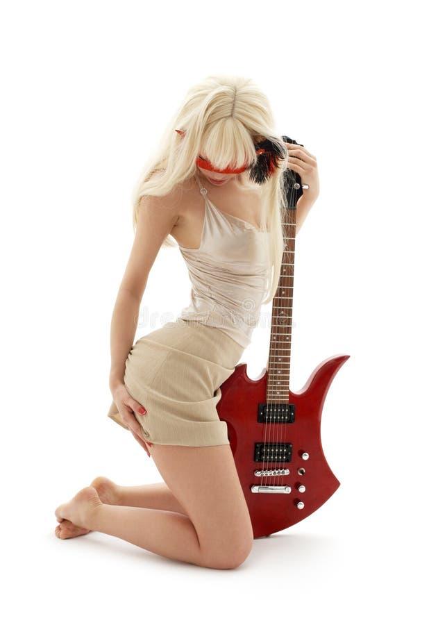 Mädchen in der Schablone mit roter Gitarre lizenzfreies stockfoto