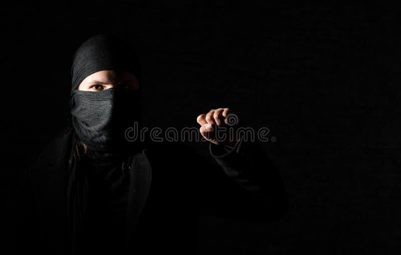 Mädchen in der schwarzen Kleidung mit den versteckten Gesichtsprotesten, die Faust auf schwarzem Hintergrund mit Kopienraum anheb stockfotos