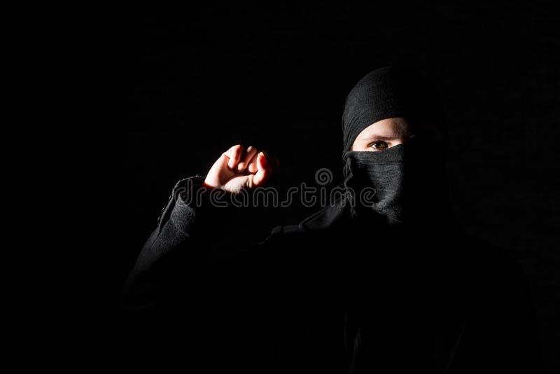 Mädchen in der schwarzen Kleidung mit den versteckten Gesichtsprotesten, die Faust auf schwarzem Hintergrund mit Kopienraum anheb stockfoto