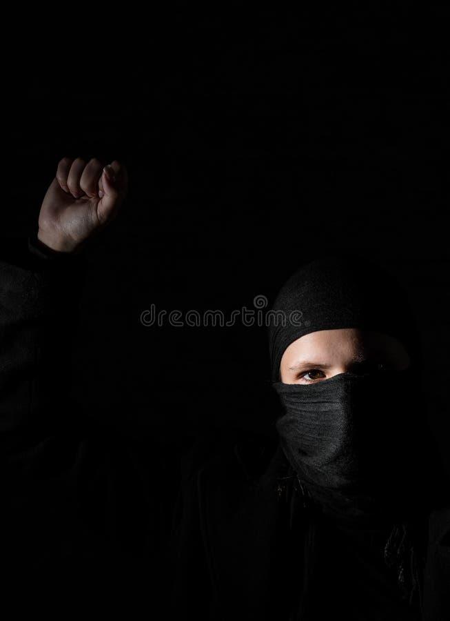 Mädchen in der schwarzen Kleidung mit den versteckten Gesichtsprotesten, die Faust auf schwarzem Hintergrund mit Kopienraum anheb lizenzfreies stockbild