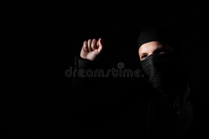 Mädchen in der schwarzen Kleidung mit den versteckten Gesichtsprotesten, die Faust auf schwarzem Hintergrund mit Kopienraum anheb lizenzfreie stockfotografie