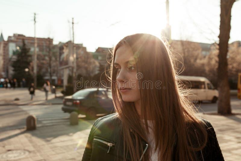 Mädchen in der Sonnenbrille auf dem Hintergrund des Sonnenuntergangs und der Stadthastigen geschäftigkeit stockbild