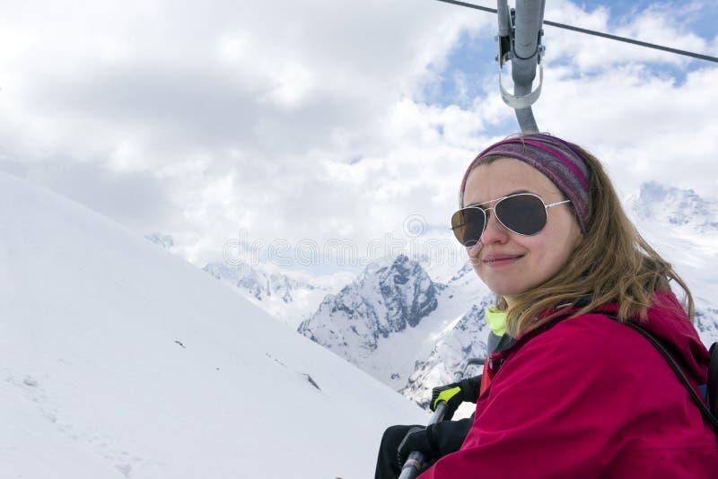 Mädchen in der Sonnenbrille auf dem Hintergrund von schneebedeckten Bergen lizenzfreie stockbilder