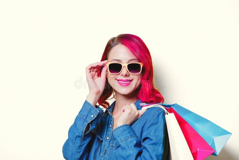 Mädchen in der Sonnenbrille, halten farbige Einkaufstaschen lizenzfreies stockbild