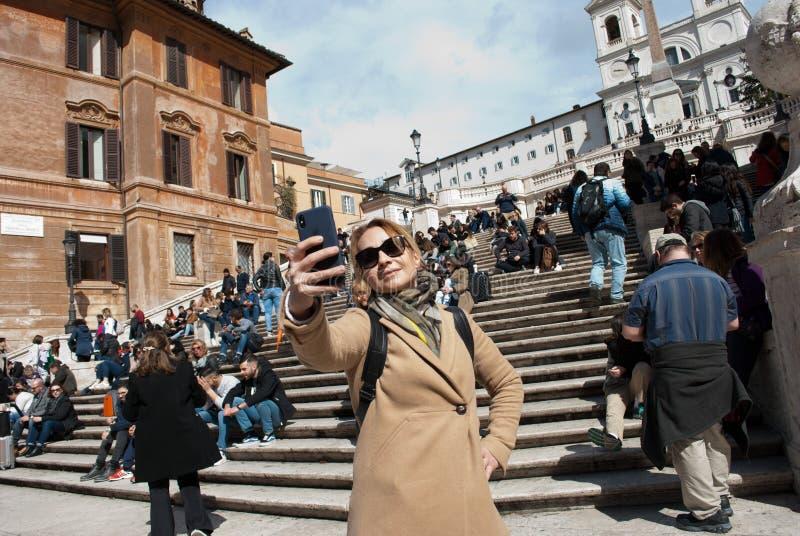 Mädchen in der Sonnenbrille macht selfie auf Treppe mit Leutehintergrund an Spanien-Quadrat an Rom-Hauptstadt von Italien im Febr lizenzfreies stockfoto
