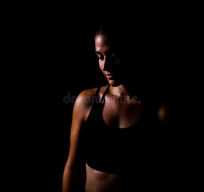 Mädchen in der Sportabnutzung, die hinunter lokalisiert mit zurückhaltendem Schuss des schwarzen Hintergrundes schaut stockfotos