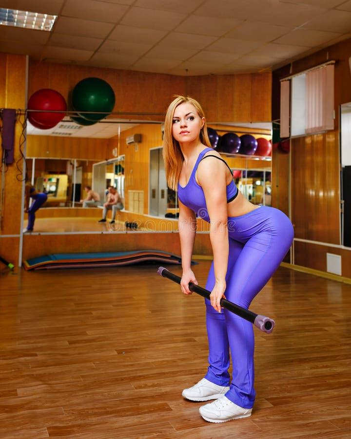 Mädchen in der Turnhalle mit Körperstange stockfotografie