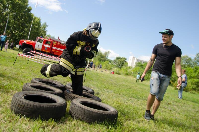 Mädchen in der Uniform des Feuerwehrmannes springt auf Hinderniskurs des Reifens lizenzfreies stockfoto