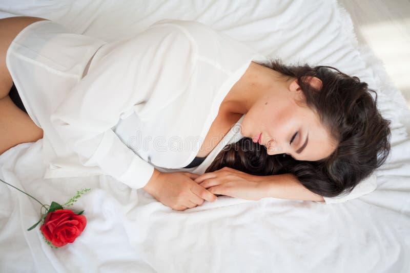 Mädchen in der Wäsche, die auf einem Bett mit einer Rose liegt stockbild