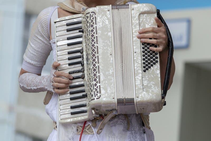 Mädchen in der weißen Kleidung spielt das weiße Akkordeon stockfotografie