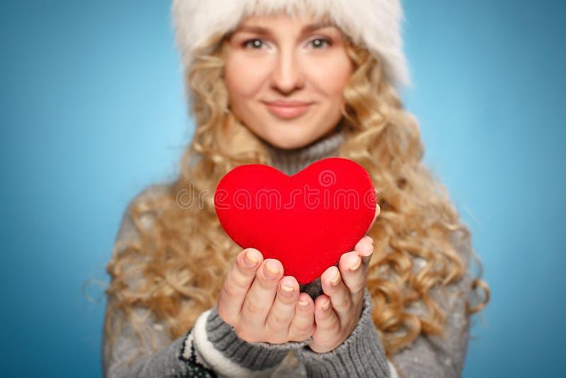 Mädchen in der Winterkleidung, die Herz gibt. Konzept des Valentinstags stockbild