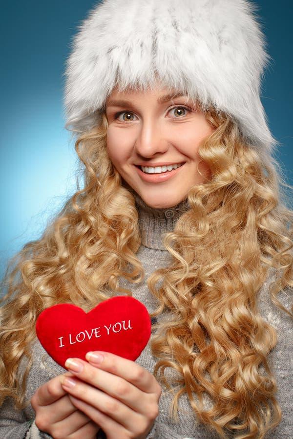 Mädchen in der Winterkleidung, die Herz gibt. Konzept des Valentinstags lizenzfreies stockbild