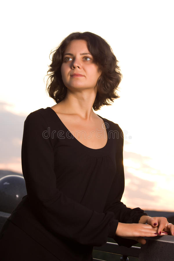 Mädchen des dunklen Haares im schwarzen Kleid lizenzfreie stockfotos