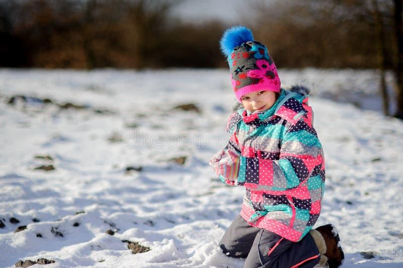 Mädchen des jüngeren schulpflichtigen Alters im hellen Skianzug machte einen Schneeball stockbilder