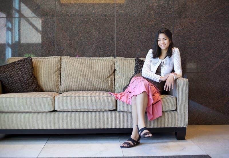 Mädchen des jungen jugendlich, das auf einer eleganten Couch stillsteht lizenzfreie stockfotos