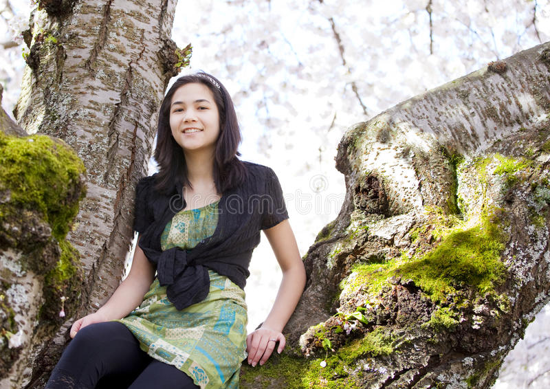 Mädchen des jungen jugendlich, das auf Niederlassungen des blühenden Kirschbaums sitzt lizenzfreie stockfotos