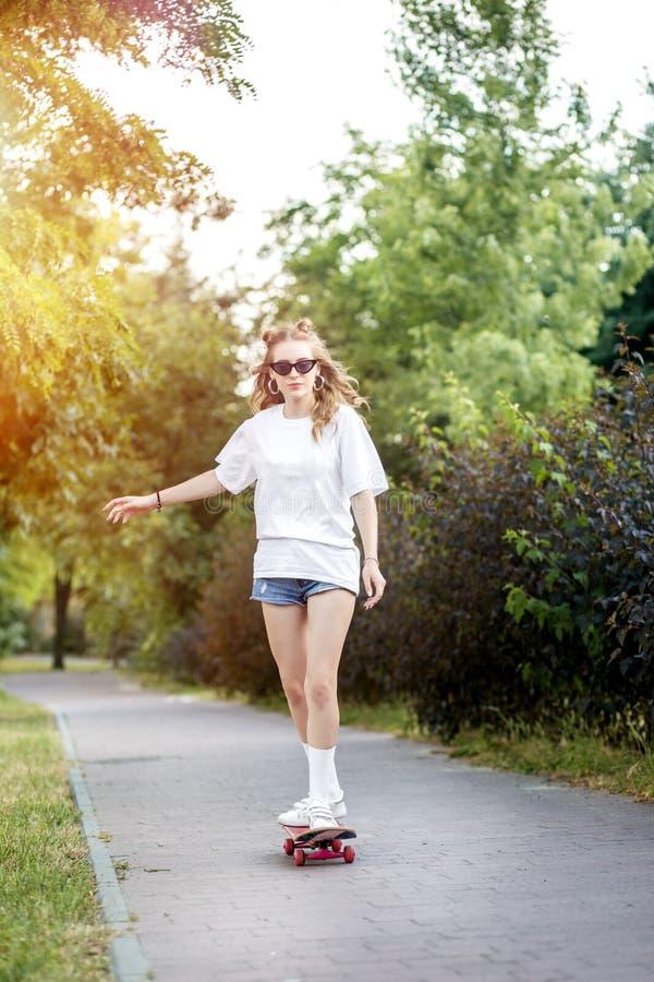 Mädchen des jungen jugendlich, das ein Rochenbrett im Park reitet Das Konzept des Lebensstils, Freizeit lizenzfreie stockfotos