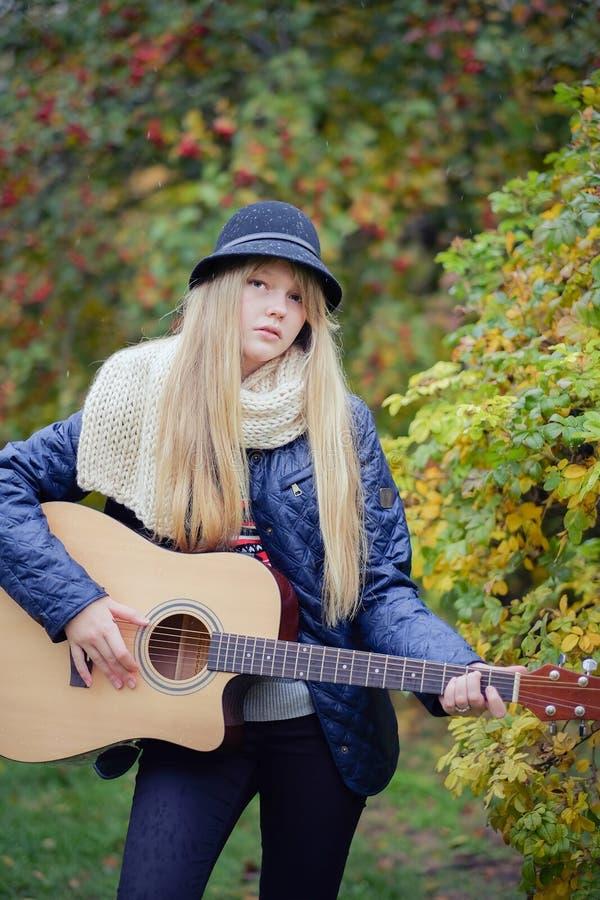 Mädchen des jungen jugendlich, das Gitarre im Park spielt lizenzfreie stockfotos
