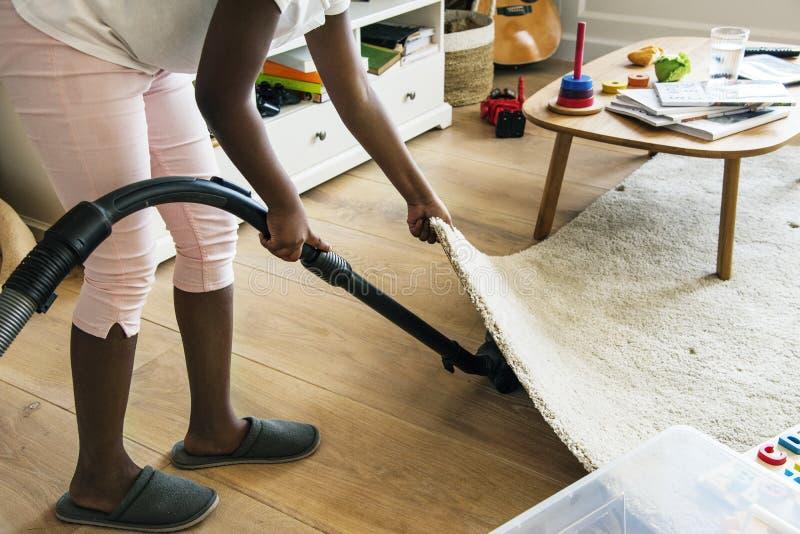 Mädchen des jungen jugendlich, das herauf das Haus Staub saugt lizenzfreies stockfoto