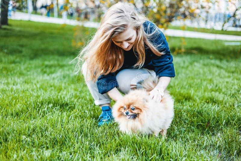 Mädchen des jungen jugendlich, das mit ihrem Hund-Pomeranian-Spitz auf dem gra spielt lizenzfreies stockbild