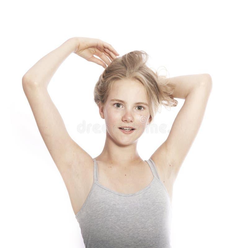 Mädchen des jungen jugendlich hält blondes Haar oben gegen weißen Hintergrund lizenzfreie stockfotografie