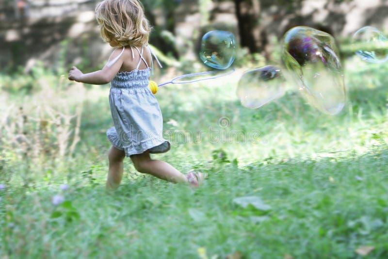 Mädchen des jungen Kindes, das große Seifenluftblasen durchbrennt stockbild