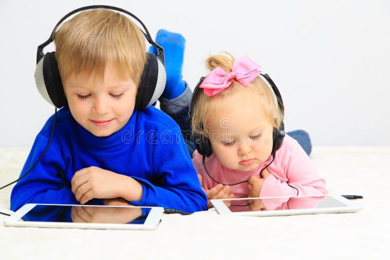 Mädchen des kleinen Jungen und des Kleinkindes mit Kopfhörer unter Verwendung lizenzfreie stockbilder