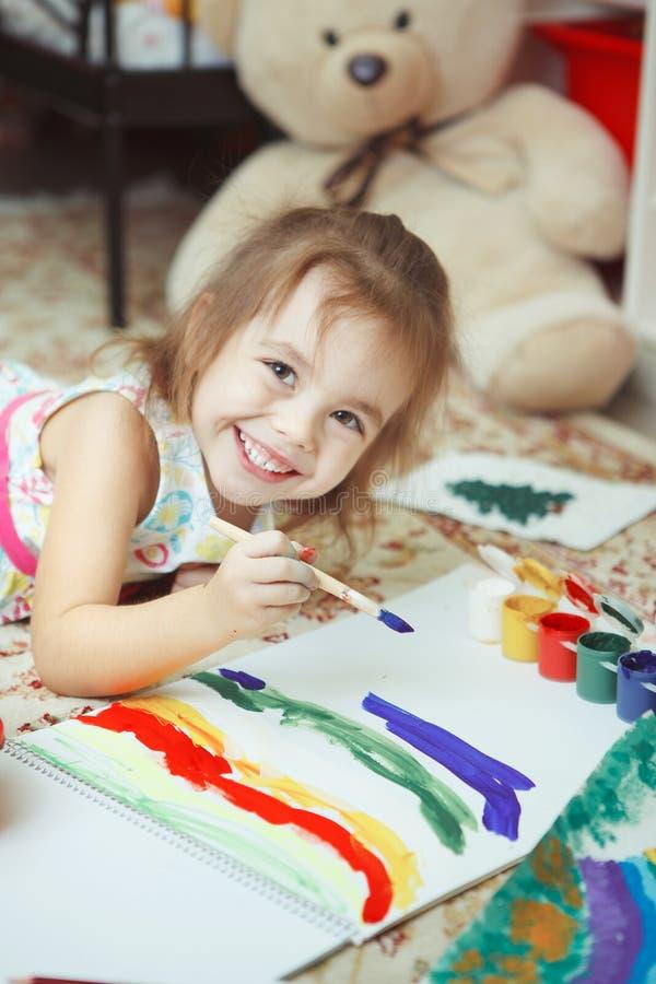 Mädchen des Malereiregenbogens der guten Laune mit Bürste stockfoto