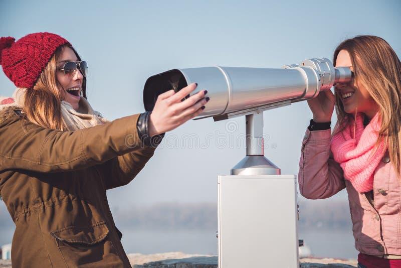 Mädchen, die über Panoramafernglasteleskop kämpfen stockbilder